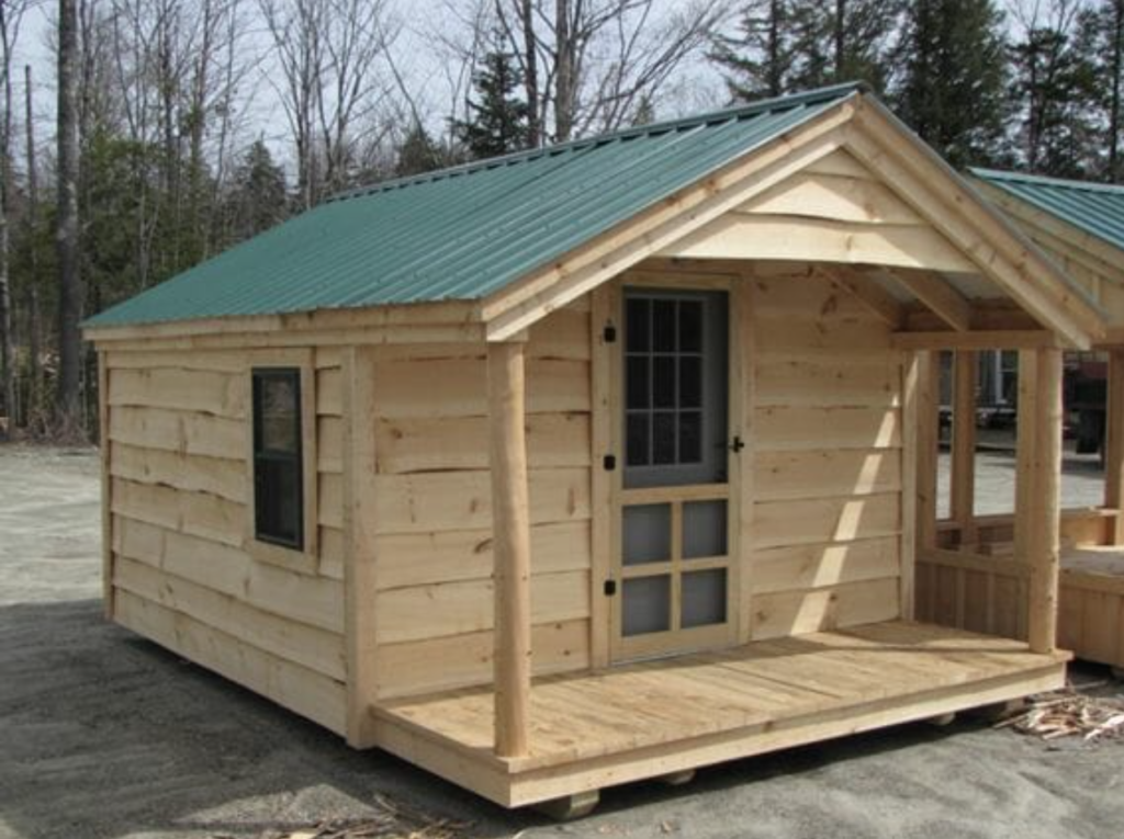 photograph of a 12' x 20' shed with a small porch and an overhang roof above the porch. The building's short side is frontward, with a door centered. There is live edge siding, as you'd find in the first few cuts of a milled log as you work to square angles.  The roof of the building is metal (green).